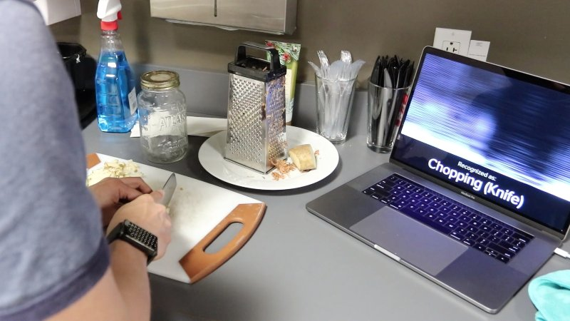 A student tests the Carnegie Mellon smartwatch that detects hand motion activity and the smartwatch detects chopping a vegetable.